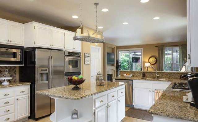 32Crawford Tustin The kitchen adorns stainless steal appliances including refriger