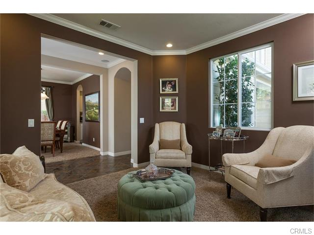 The formal living room has a view of the yard and crown molding.