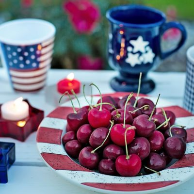 Patriotic Cocktails Bowl of Cherries sitting on a table with Coffee Mugs Around it