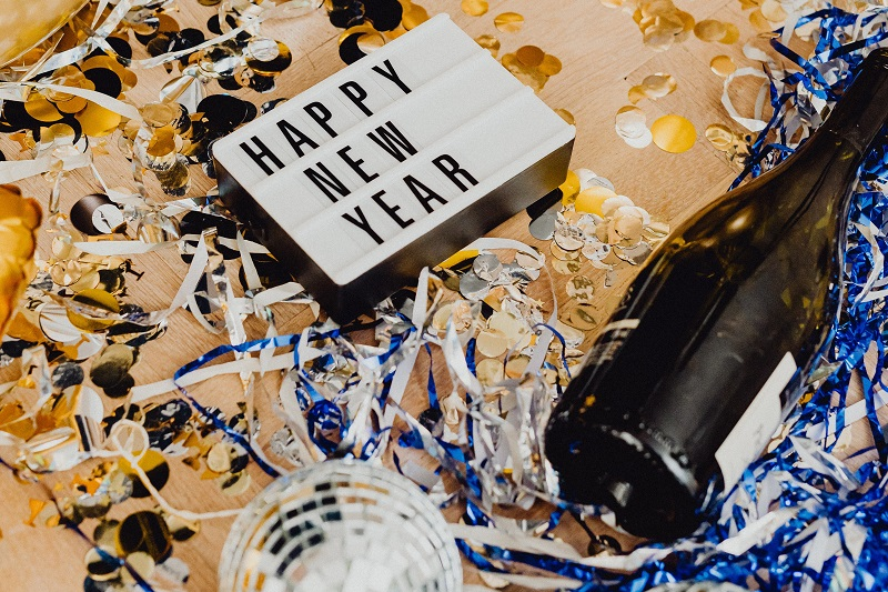 Inspiring Margarita Recipes Sign with Happy New Year on it Next to a Champagne Bottle Covered in Confetti