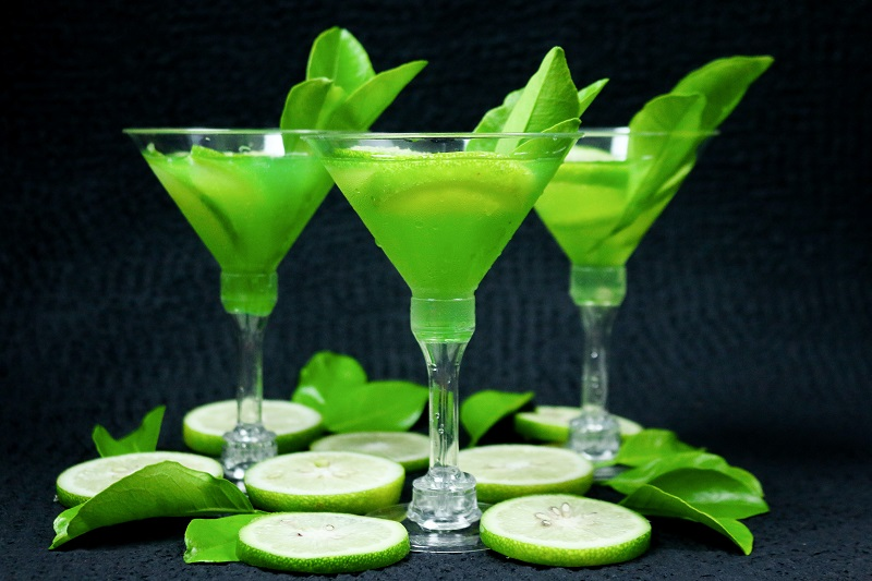 St. Patrick's Day Green Cocktails Three Martini Glasses with Green Liquid Inside and Lime Slices Around Them