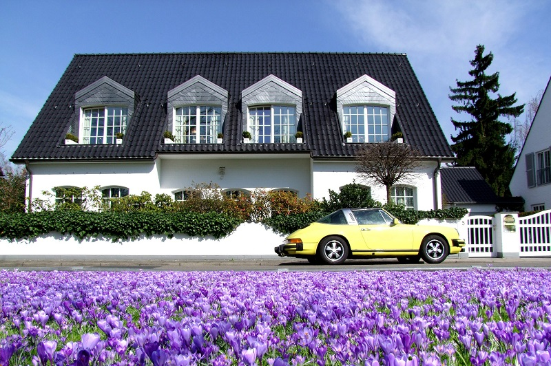 Reasons to Move to Orange County California View of a Home from the Outside with Purple Flowers and a Yellow Car Parked in Front